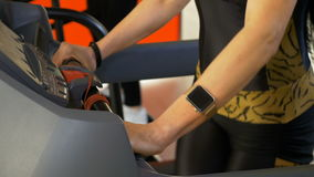 Sportive woman wearing smartwatch doing sport activity on the treadmill stock footage