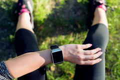 Sportive Woman After Workout Session Checking Fitness Results on Smart Watch. Top view shot of woman checking fitness progress Stock Photos