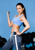 Sportive woman works out with dumbbells Royalty Free Stock Photography