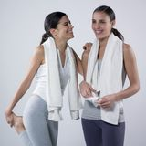 Sportive women. A studio portrait of two young women making a pause after  exercises and smiling Royalty Free Stock Image