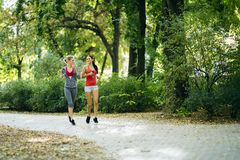 Sportive women jogging in park. And listening to music through earphones Royalty Free Stock Image