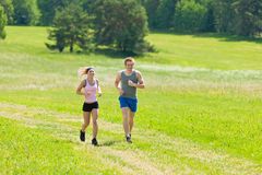 Sportive young couple jogging meadows sunny summer. Young fit couple jogging on summer day in meadows countryside Royalty Free Stock Image