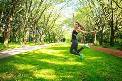 Sportive young fitness woman jumping in summer park. Freedom concept Stock Photos