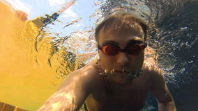 Sportive young guy in the swimming pool, underwater view. Vacation summer time. Action camera. Happy handsome young man swimming in the swimming pool, underwater stock video