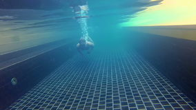 Sportive young guy in the swimming pool, underwater view. Vacation summer time. Action camera. Happy handsome young man swimming in the swimming pool, underwater stock video footage
