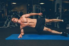 Sportive young man doing side plank royalty free stock photography