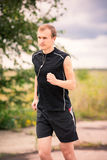 Sportive young man jogging outdoor Royalty Free Stock Photography