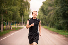 Sportive young man jogging outdoor Stock Photos