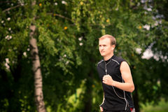 Sportive young man jogging outdoor Royalty Free Stock Photos