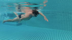 Sportive young man swimming crawl style in swimming pool, underwater view. Vacation. Action camera. Sportive young man swimming crawl style in the swimming pool stock footage