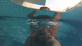 Sportive young man in the swimming pool, underwater view. Vacation summer time. Action camera. Happy handsome young man swimming in the swimming pool, underwater stock footage