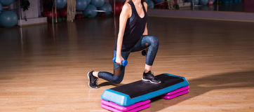 Sportive young woman with beautiful athletic body doing exercises with dumbbells close-up. Fitness, bodybuilding. Sportive young woman with beautiful athletic Royalty Free Stock Images