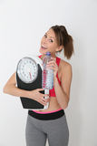 Sportive young woman with bottle of water and scale Stock Photos