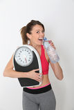 Sportive young woman with bottle of water and scale Stock Image