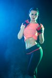 Sportive young woman between bright green and blue lights Royalty Free Stock Images