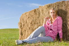 Sportive young woman relax by bales sunset. Sportive young woman relax lean against hay bales sunset countryside Royalty Free Stock Photos