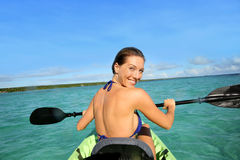Sportive young woman rowing in a kayak. Back view of beautiful woman paddling in canoe royalty free stock images