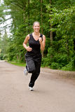 Sportive young woman running over a forrest road Stock Images