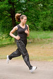 Sportive young woman running over a forrest road Stock Photo