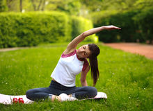 Sportive young woman stretching, doing fitness exercises in park Stock Photos