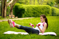 Sportive young woman stretching with dumbbells, doing fitness Royalty Free Stock Images