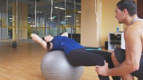 Sportive young woman with fitness instructor doing abdominal crunches on fitballs. Sportive young women with fitness instructor doing abdominal crunches on Stock Photo