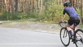 Sportiver geeigneter weiblicher Radfahrer, der aus dem Sattel im Park heraus radelt Hartes Training auf Fahrrad Radfahrenkonzept