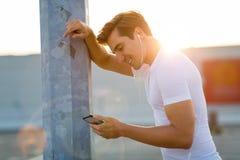 Sportiver junger Mann in der Stadt mit Smartphone stockfotos