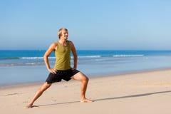 Sportiver Mann, der Gymnastik auf dem Strand tut Stockfoto