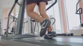 Sportiver Mann, der oben auf Tretmühle, Abschluss von Füßen, Trainingstraining in der Eignungsmitte läuft stock video footage