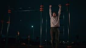 Sportiver Mann hebt die Beine an, die am Freien der horizontalen Bar in der Nacht hängen stock footage
