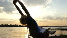 Sportiver Mann sitzt, liest, tut eine Übung auf einem Riverbank bei Sonnenuntergang stock video