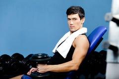 Sportiver Mann steht still, ein Gewicht in der Hand anhalten Stockfoto