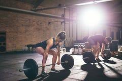 Sportiver Mann und Frau, die in der Turnhalle deadlifting ist Lizenzfreie Stockfotografie