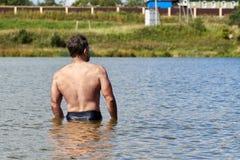 Sportiver Mann von mittlerem Alter badet im kleinen Vorstadtsee im Sommer R?ckseitige Ansicht lizenzfreies stockbild