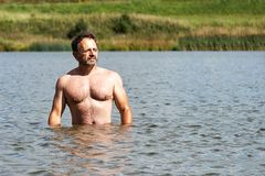 Sportiver Mann von mittlerem Alter badet im kleinen Vorstadtsee im Sommer stockfotos