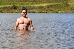 Sportiver Mann von mittlerem Alter badet im kleinen Vorstadtsee im Sommer stockfotografie