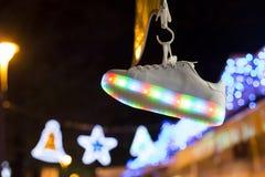 Sportiver Schuh, der an unscharfem Hintergrund von Lichtern in der Dunkelheit hängt Lizenzfreie Stockfotografie