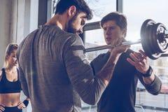Sportivi che si esercitano con il bilanciere e la sportiva che stanno dietro all'allenamento della palestra Fotografie Stock