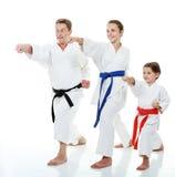 Sportivi della famiglia due sorelle con suo padre in un braccio della perforazione del battito del kimono Immagini Stock Libere da Diritti