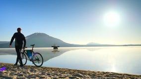 Sportivo alto che spinge bicicletta in sabbia bagnata della spiaggia del lago della montagna Tempo soleggiato della molla sulla s video d archivio