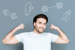Sportivo bello che mostra i suoi muscoli e che sembra sicuro fotografie stock