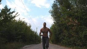 Sportivo bello che sprinta velocemente lungo la strada con bello paesaggio al fondo Giovane uomo muscolare con la radio video d archivio