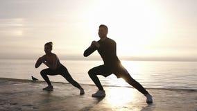 Sportivo caucasico determinated giovani ed il suo partner femminile con l'allungamento delle gambe prima della mattina di ogni gi archivi video