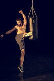 Sportivo caucasico giovane che dà dei calci al punching ball Fotografia Stock