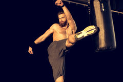 Sportivo caucasico giovane che dà dei calci al punching ball Fotografia Stock Libera da Diritti