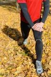 Sportivo che allunga le gambe Immagine Stock