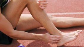 Sportivo che danneggia il suo piede stock footage