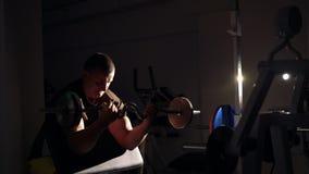 Sportivo che fa esercizio con il bilanciere per il bicipite nella palestra 4k archivi video