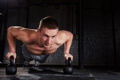 Sportivo che fa esercizio di spinta-UPS con kettlebell in un allenamento del crossfit contro il muro di mattoni Fotografia Stock Libera da Diritti